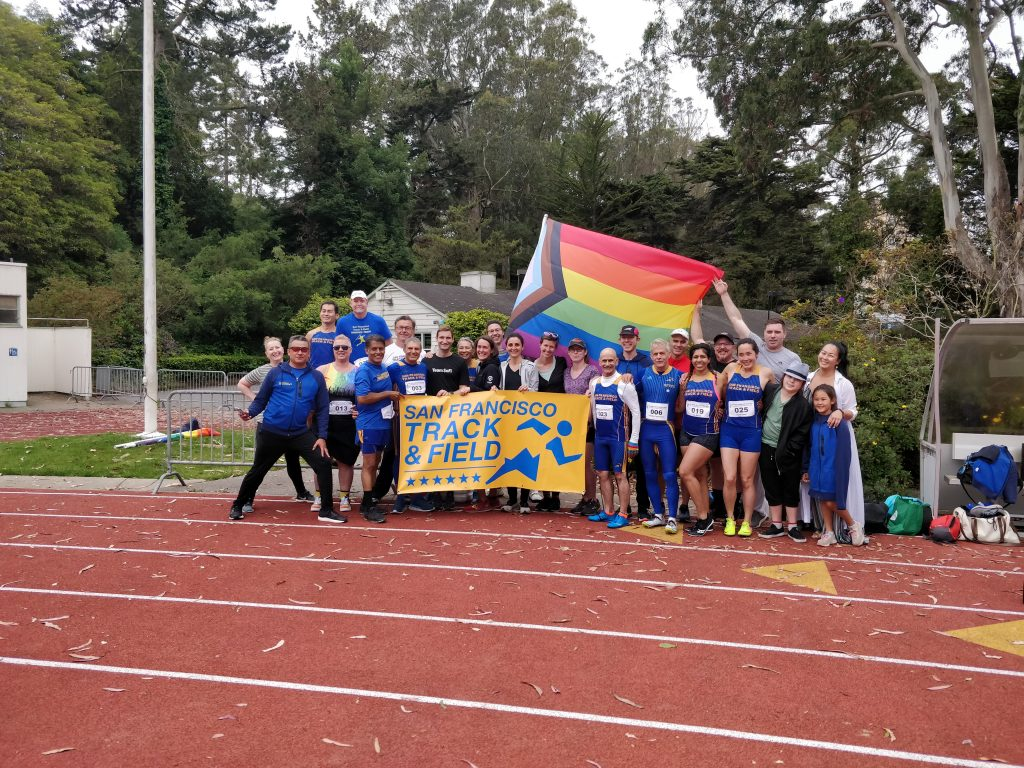 san francisco track club posing with banner and flag